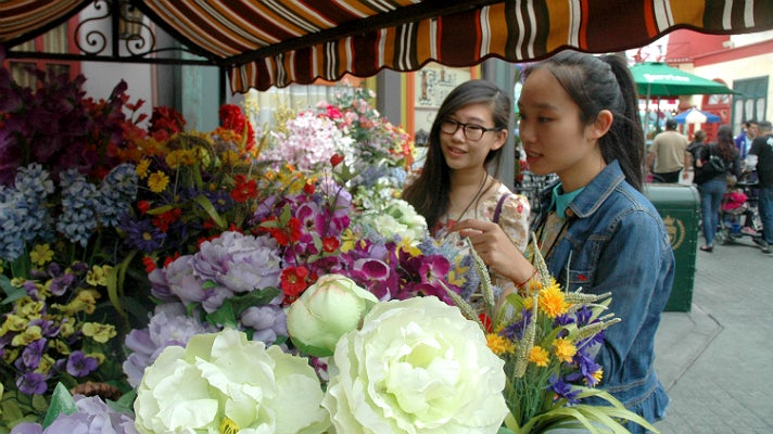 """Sally Guo and Susanna Niu admire the flowers in """"Paris"""" at Universal Studios Hollywood"""