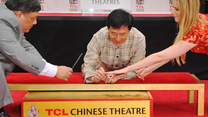 Jackie Chan signs his name at the TCL Chinese Theatre