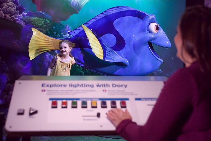 "Visitors adjust the lighting for their photo with Dory at ""The Science Behind Pixar"""