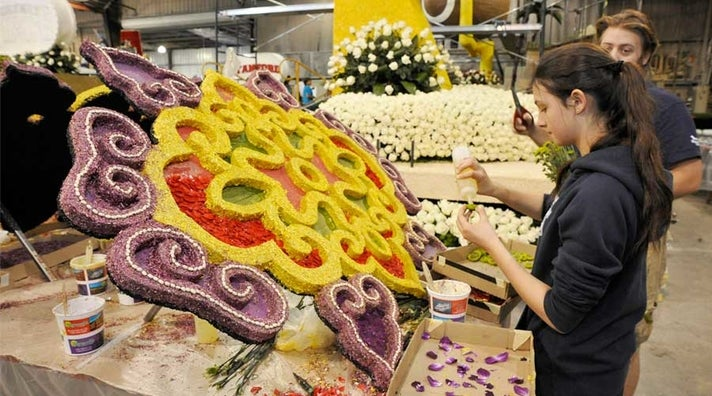 Volunteers decorate a Rose Parade float